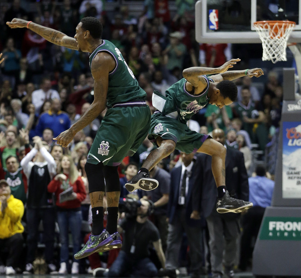Photo - Milwaukee Bucks' Larry Sanders (8) and Brandon Jennings celebrate after teammate Monta Ellis made a three-point basket in the final seconds of an NBA basketball game against the Orlando Magic, Sunday, March 17, 2013, in Milwaukee. The Bucks won 115-109. (AP Photo/Morry Gash)