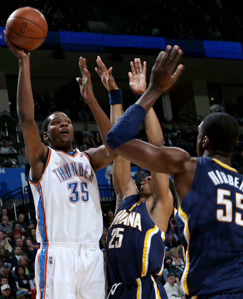 Photo - Oklahoma City's Kevin Durant looks for an open shot despite pressure from Indiana's Brandon Rush and Roy Hibbert during the NBA basketball game between the Indiana Pacers and the Oklahoma City Thunder at the Ford Center in Oklahoma City, Sunday, April 5, 2009. Photo by John Clanton, The Oklahoman