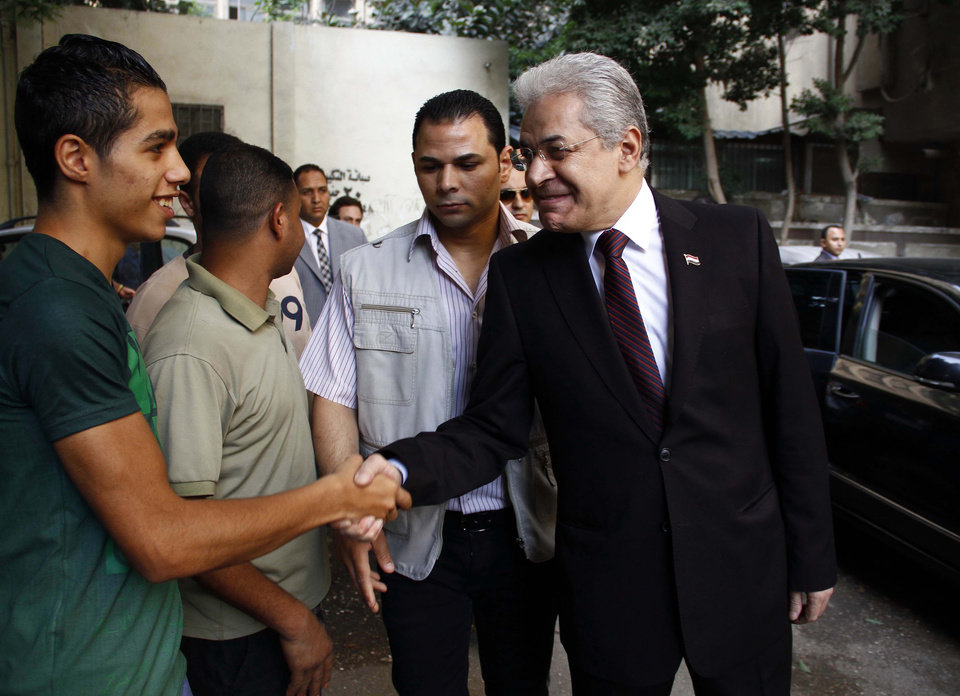 Photo - Presidential candidate Hamdeen Sabahi shakes hands with a civilian near a polling site on the first day of the presidential elections in Cairo, Egypt, Monday, May 26, 2014. Retired military chief Field Marshal Abdel-Fattah el-Sissi is practically assured of a victory in the vote, which is being held over two days, Monday, 26, and Tuesday, 27. The only other candidate in the race is leftist politician Sabahi, who finished third in the 2012 presidential election. (AP Photo/Ahmed Abdel Fattah, El Shorouk Newspaper) EGYPT OUT