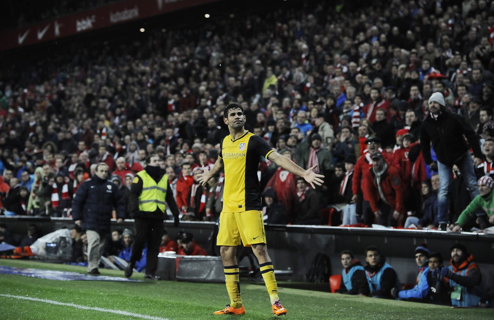 Photo - Atletico de Madrid's Diego Costa of Brazil, celebrates beside Athletic Bilbao's supporters after scoring his goal, during their Spanish Copa del Rey round-8 second leg soccer match against Athletic Bilbao, at San Mames stadium, in Bilbao, northern Spain, Wednesday, Jan. 29, 2014. (AP Photo/Alvaro Barrientos)