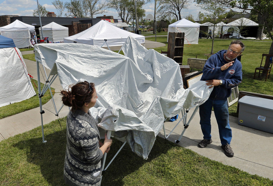 Photo - Jeweler Hilary Davis, with Take Heart Jewelry, gets neighborly advice from Jim Barton, Fargo, N.D., maker of children's toy bows, as she sets up her tent on Friday, May 3, 2013, in Norman, Okla. in preparation for the May Fair Arts Festival at Andrews Park. Photo by Steve Sisney, The Oklahoman