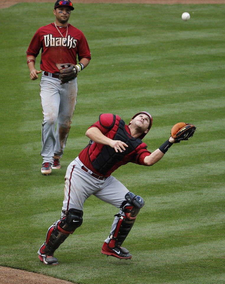 Photo - Arizona Diamondbacks catcher Miguel Montero catches a pop-up as teammate Martin Prado watches, against the Chicago Cubs during the third inning of a spring training baseball game, Thursday, Feb. 27, 2014, in Mesa, Ariz. (AP Photo/Matt York)