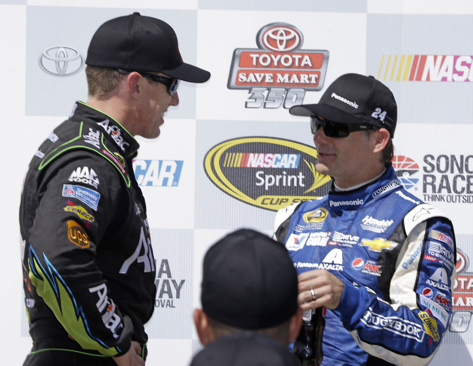 Photo - Carl Edwards, left is congratulated by Jeff Gordon, right, after winning the NASCAR Sprint Cup Series auto race Sunday, June 22, 2014, in Sonoma, Calif. Edwards won the race and Gordon finished second. (AP Photo/Eric Risberg)