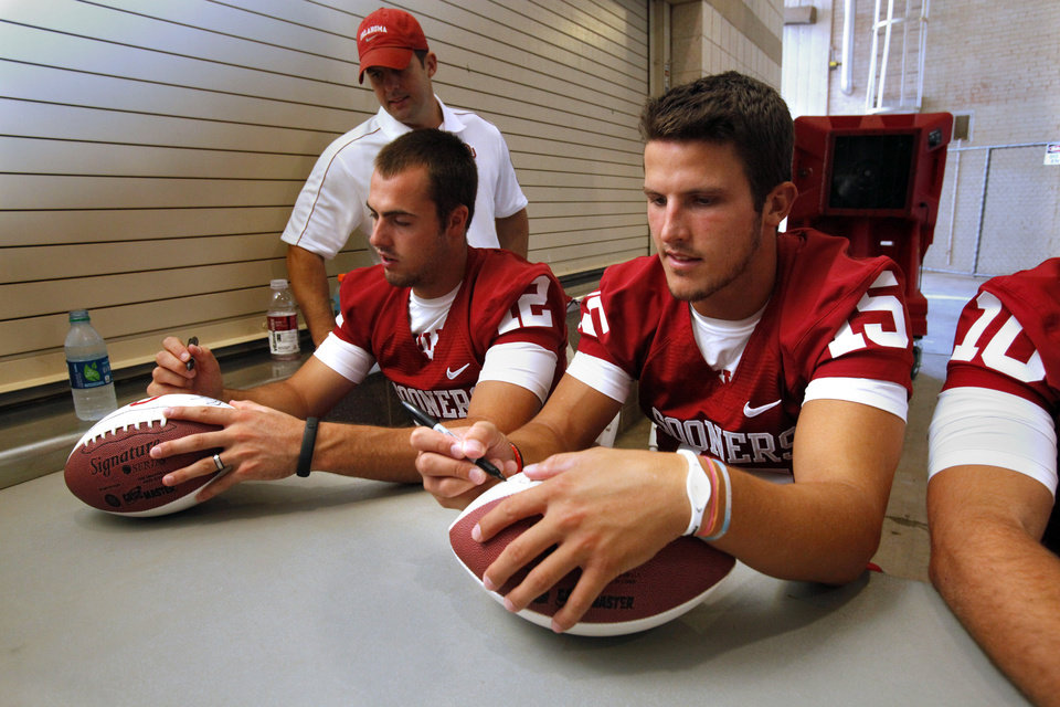 Photo - Quarterbacks Landry Jones and Drew Allen sign autographs during the Meet the Sooners event inside Gaylord Family/Oklahoma Memorial Stadium at the University of Oklahoma on Saturday, Aug. 4, 2012, in Norman, Okla.  Photo by Steve Sisney, The Oklahoman