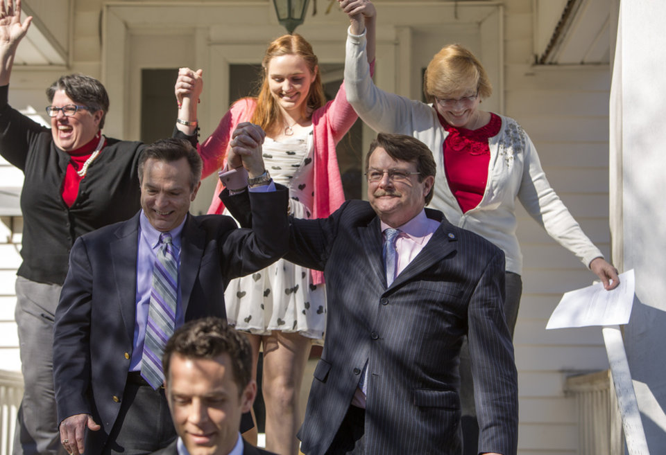 Photo - From left back row, Carol Schall , Emily Schall-Townley,16,  daughter of Schall and Townley and Mary Townley , Tim Bostic and Tony London celebrate the Thursday's ruling by federal Judge Arenda Wright Allen that Virginia's same-sex marriage ban was unconstitutional on Friday, Feb. 14, 2014 in Norfolk, Va.  Wright Allen on Thursday issued a stay of her order while it is appealed, meaning that gay couples in Virginia still won't be able to marry until the case is ultimately resolved. An appeal will be filed to the 4th District Court of Appeals, which could uphold the ban or side with Wright Allen. At the bottom of photo is Adam Umhoefer, Executive Director of the American Foundation for Equal Rights.  (AP Photo/The Virginian-Pilot, Bill Tiernan)  MAGS OUT