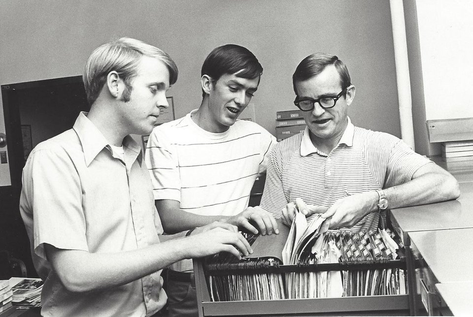 Photo -  Bill Hancock, left, in the OU sports information office in 1970 with Don McGuire and Johnny Keith. PHOTO PROVIDED