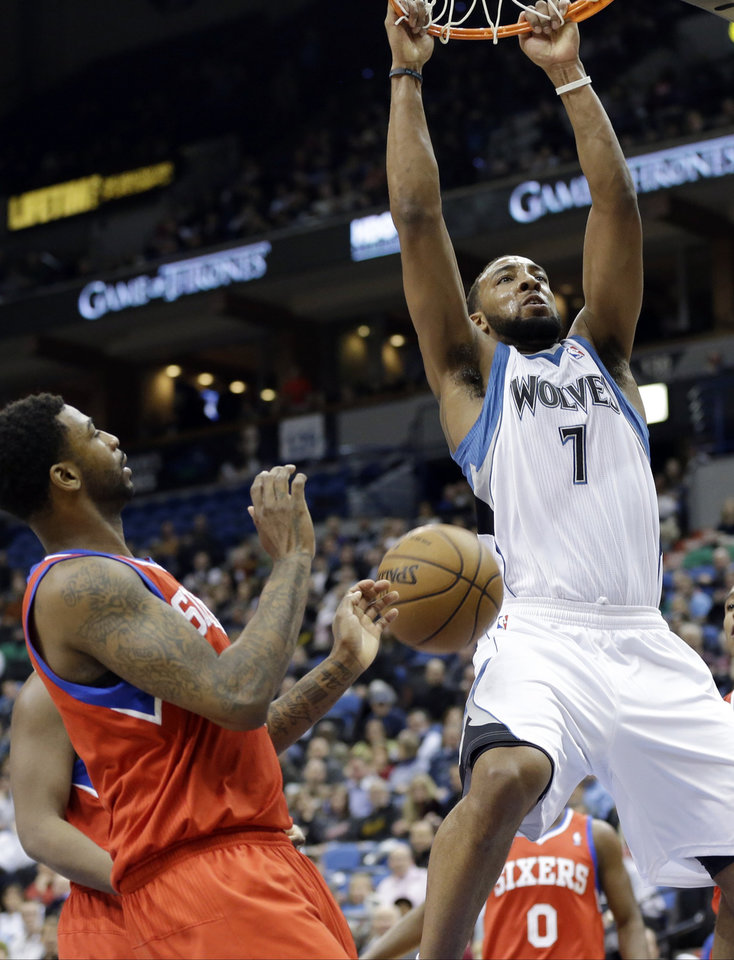 Minnesota Timberwolves' Derrick Williams, right, completes a slam as Philadelphia 76ers' Dorell Wright watches during the first quarter of an NBA basketball game Wednesday, Feb. 20, 2013, in Minneapolis. (AP Photo/Jim Mone)