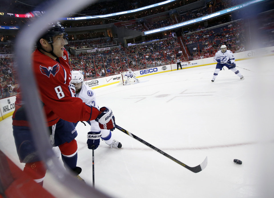 Photo - Washington Capitals right wing Alex Ovechkin (8), from Russia, passes in front of Tampa Bay Lightning defenseman Radko Gudas (7), from the Czech Republic, in the first period of an NHL hockey game on Sunday, April 13, 2014, in Washington. (AP Photo/Alex Brandon)