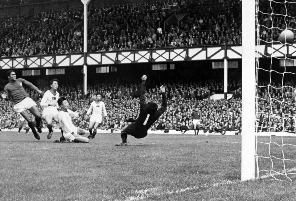 Photo - FILE - In this July 23, 1966 file photo, Portugal's Eusebio, left, scores one of his four goals during the World Cup quarterfinal match against North Korea at Goodison Park, Liverpool. Portugal defeated North Korea 5-3. Eusebio, the Portuguese football star who was born into poverty in Africa but became an international sporting icon and was voted one of the 10 best players of all time, has died of heart failure aged 71, Sunday, Jan. 5 2014. (AP Photo/Bippa, File)