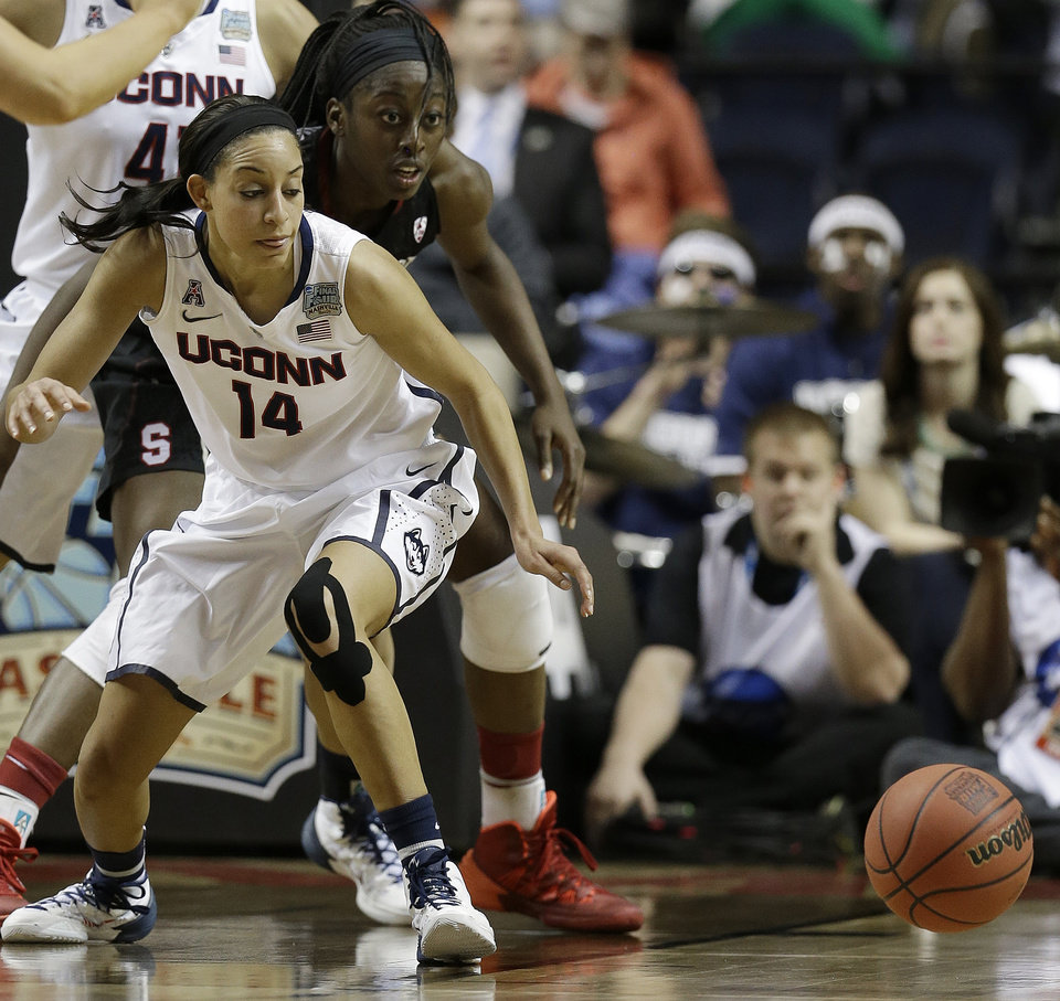 Photo - Connecticut guard Bria Hartley (14) and Stanford forward Chiney Ogwumike (13) vie for a loose ball during the first half of the semifinal game in the Final Four of the NCAA women's college basketball tournament, Sunday, April 6, 2014, in Nashville, Tenn. (AP Photo/Mark Humphrey)