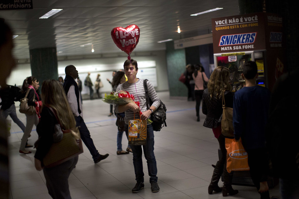Photo - Bearing gifts, Junio waits for his boyfriend Lenon in Sao Paulo's metro, Brazil, Wednesday, June 11, 2014. A threatened second round of a subway strike in Sao Paulo would cripple transportation in South America's biggest city. Authorities are counting on the subway to carry most fans to Sao Paulo games. (AP Photo/Rodrigo Abd)