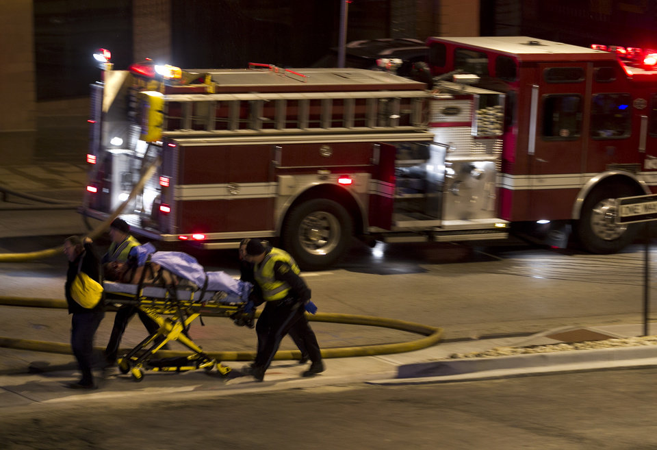 Photo - Emergency personnel wheel an injured victim from the scene of a gas explosion and massive fire Tuesday night, Feb. 19, 2013 at the Country Club Plaza in Kansas City, Mo. A car crashed into a gas main in the upscale Kansas City shopping district, sparking a massive blaze that engulfed an entire block and caused multiple injuries, police said. (AP Photo/The Kansas City Star, Tammy Ljungblad) KANSAS CITY OUT