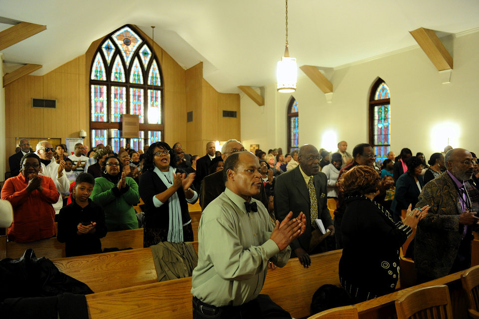 Photo - People stand and clap during the music portion of the Black History Committee's celebration of Dr. Martin Luther King, Jr's birthday at Greater Norris Chapel Baptist Church in Henderson, Ky Sunday Jan. 19, 2014. (AP Photo/The Gleaner, Darrin Phegley)