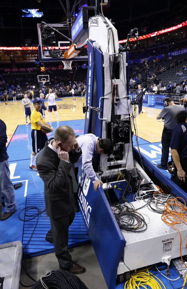 Photo - Trouble with the goal threatens to postpone an NBA basketball game where the Oklahoma City Thunder are to play the Los Angeles Lakers at the Chesapeake Energy Arena in Oklahoma City, on March 13, 2014.  Workers check out the goal standard after a porblem was noticed before the game.  Photo by Steve Sisney The Oklahoman