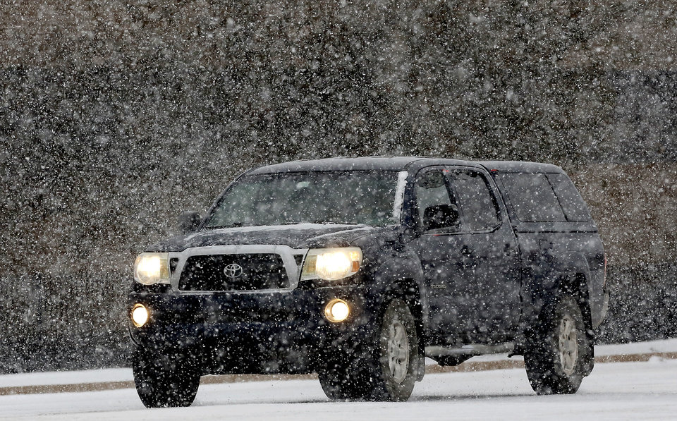Photo - A truck travels on NE 63 Street as a strong winter storm, bringing snow and ice,  moved across the state and through the metro area Thursday afternoon, Dec. 5, 2013. Photo by Jim Beckel, The Oklahoman