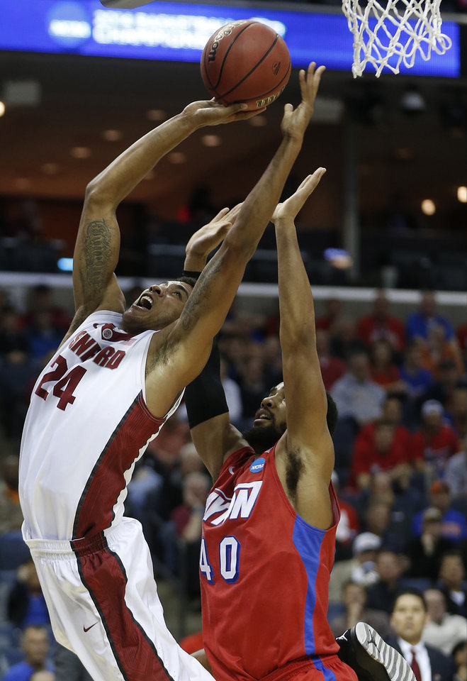 Photo - CORRECTS DAYTON PLAYER TO DEVON SCOTT, INSTEAD OF KHARI PRICE - Stanford forward Josh Huestis (24) shoots against Dayton's Devon Scott (40) during the first half in a regional semifinal game at the NCAA college basketball tournament, Thursday, March 27, 2014, in Memphis, Tenn. (AP Photo/John Bazemore)