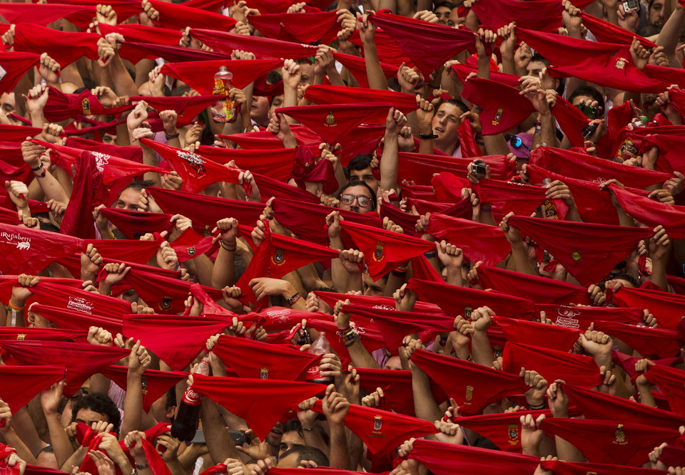 Photo - Revelers hold up traditional red neckties during the launch of the