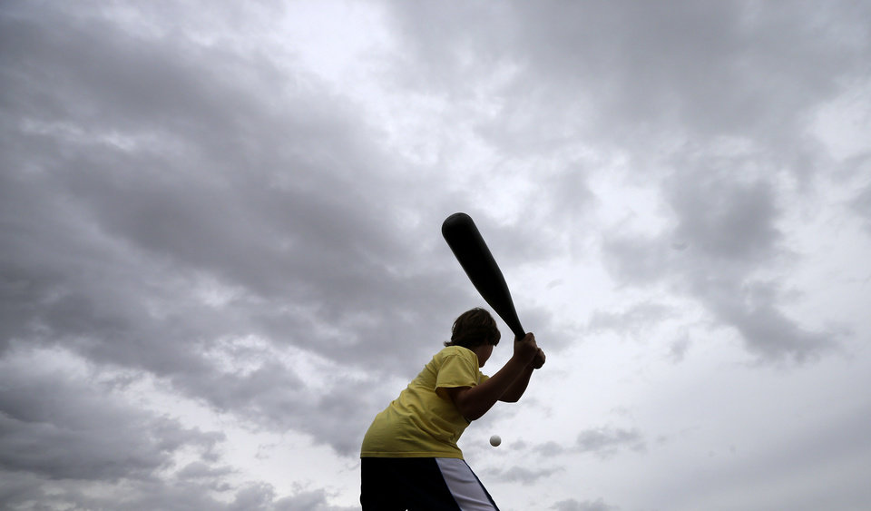 Photo - Oakland Athletics fan Shane Straw, of Sacramento, Calif., swings at a plastic ball under heavy clouds while waiting for the start of a spring training baseball game between the Athletics and the Texas Rangers Saturday, March 1, 2014, in Phoenix. Spring training games continued Saturday, as Arizona awaited more possible rainfall from a large storm that wreaked havoc on Southern California Friday. (AP Photo/Gregory Bull)