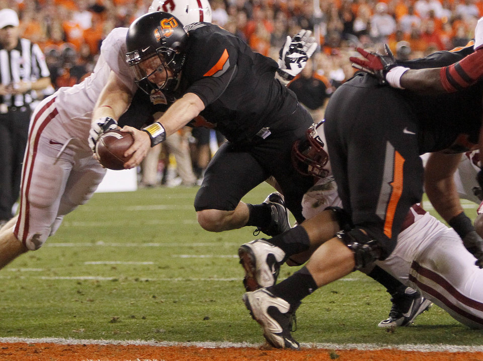 Photo - Oklahoma State quarterback Brandon Weeden lunges across the goal line for a touchdown against Stanford during the first half of the Fiesta Bowl NCAA college football game Monday, Jan. 2, 2012, in Glendale, Ariz. (AP Photo/Matt York)