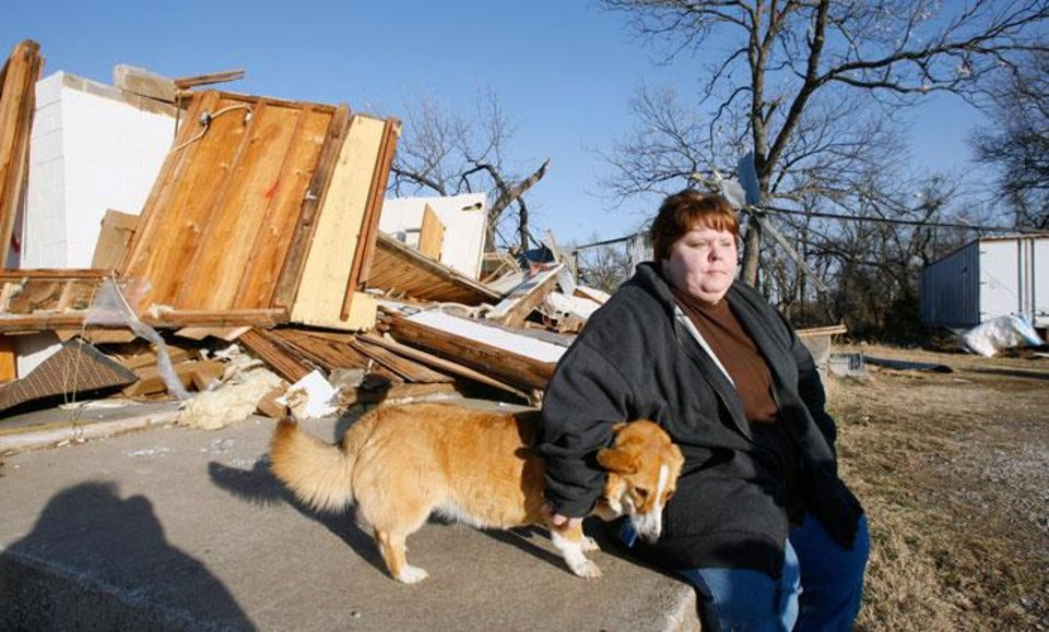 Photo -  Trina Quinton sits with a lost dog at her cousin's destroyed furniture store, John's Furniture, on the north side of SH 70 in Lone Grove Wednesday, Feb. 11, 2009. BY PAUL B. SOUTHERLAND, THE OKLAHOMAN