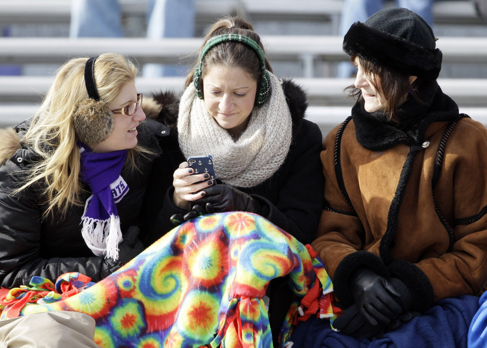 Photo -   As temperatures drop below freezing, fans bundle up to watch Illinois play against Northwestern during the first half of an NCAA college football game in Evanston, Ill., Saturday, Nov. 24, 2012. Northwestern won 50-14. (AP Photo/Nam Y. Huh)