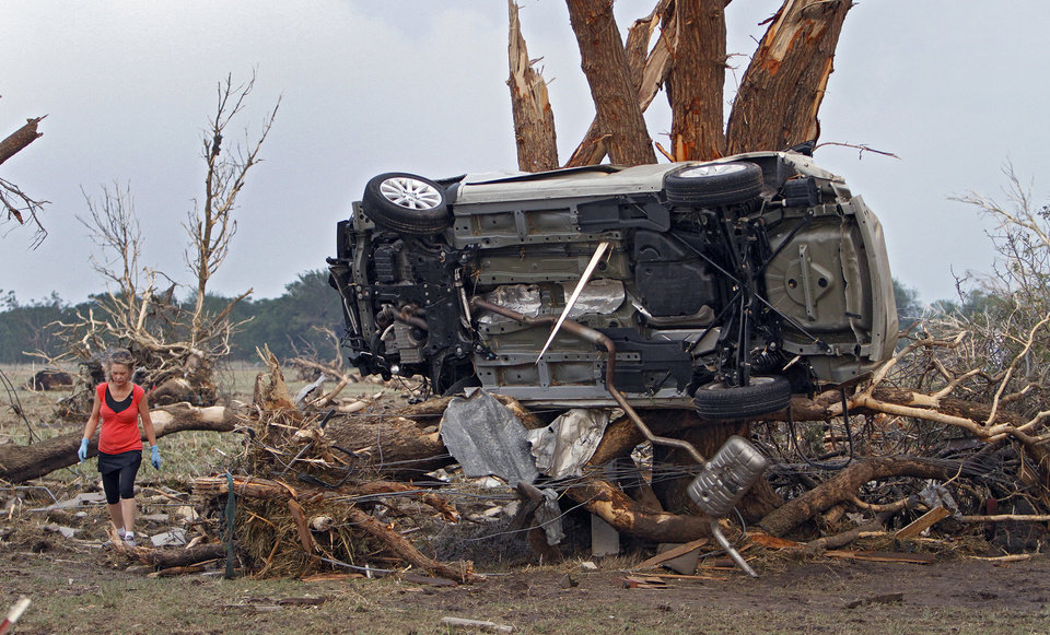 Rebecca Watts walks by a car stuck in a tree after being destroyed by a tornado north of El Reno, Okla. on Tuesday, May 24, 2011. The high-powered storms arrived Tuesday night and early Wednesday, just days after a massive tornado tore up the southwest Missouri city of Joplin. Photo by Chris Landsberer, The Oklahoman