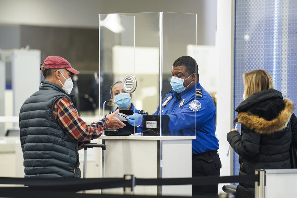 Photo - A Transportation Security Administration agent serves a traveler at a checkpoint in a sparsely populated Terminal B at LaGuardia Airport, Wednesday, Nov. 25, 2020, in the Queens borough of New York.[AP Photo/John Minchillo]
