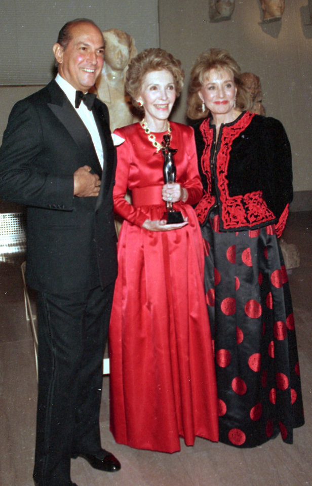 Photo - FILE - This Jan. 10, 1989 file photo shows fashion designer Oscar de la Renta, left, and journalist Barbara Walters, right, posing with first lady Nancy Reagan at the Metropolitan Museum of Art in New York City, where the first lady was awarded the Council of Fashion Designers of America's Lifetime Achievement Award for her contributions to fashion. Living in the White House has its perks, but a clothing allowance is not one of them. First ladies feel all sorts of pressure to project a fashionable look, and over the decades they've tried a range of cash-saving strategies to pull it off without going broke. Mrs. Reagan was criticized by some for wearing borrowed designer clothes, sometimes without returning them or reporting them as gifts. (AP Photo/Ed Bailey, File)