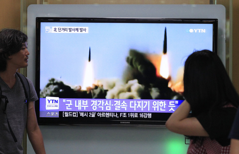Photo - People watch a TV news program showing the missile launch conducted by North Korea, at Seoul Railway Station in Seoul, South Korea, Thursday, June 26, 2014. North Korea fired three short-range projectiles Thursday into the waters off its east coast, a South Korean defense official said. The move was most likely a routine test-firing, but the official said it could also be meant to stoke tensions with Seoul. The writing on the screen reads