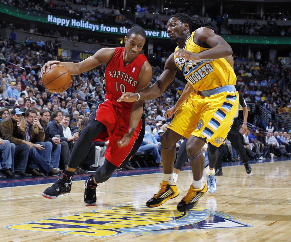 Photo - Toronto Raptors guard DeMar DeRozan, left, works the ball inside past Denver Nuggets forward Kenneth Faried during the first quarter of an NBA basketball game in Denver on Monday, Dec. 3, 2012. (AP Photo/David Zalubowski)