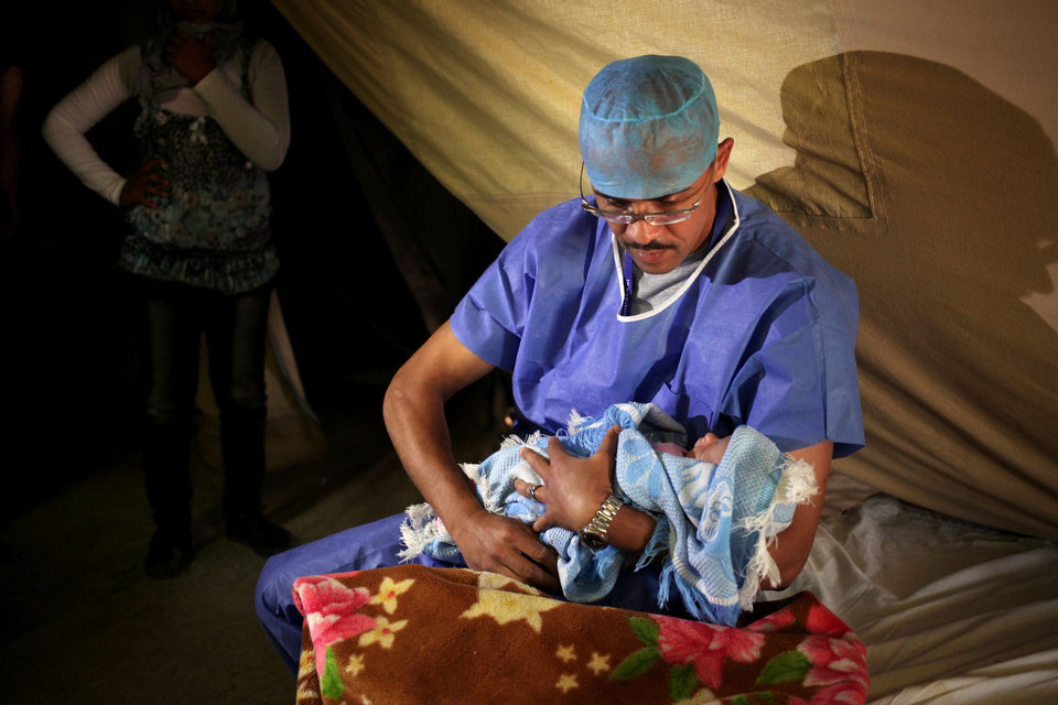 In this Monday, May 6, 2013 photo, an obstetrician holds a baby after delivery at the Moroccan field hospital in Zaatari refugee camp near the Syrian border,  in Mafraq, Jordan. Pregnant Syrian women say they never imagined giving birth outside their beloved homeland and inside a tough desert refugee camp across the border in Jordan where they battle heat, dust and to get enough drinking water. But doctors at the Zaatari camp boast of delivering more than a dozen of Syrian babies every day there. Among the births are at least two, sometimes up to five Caesarian sections, performed exclusively at the Moroccan field hospital, run by the North African state's military. (AP Photo/Mohammad Hannon)