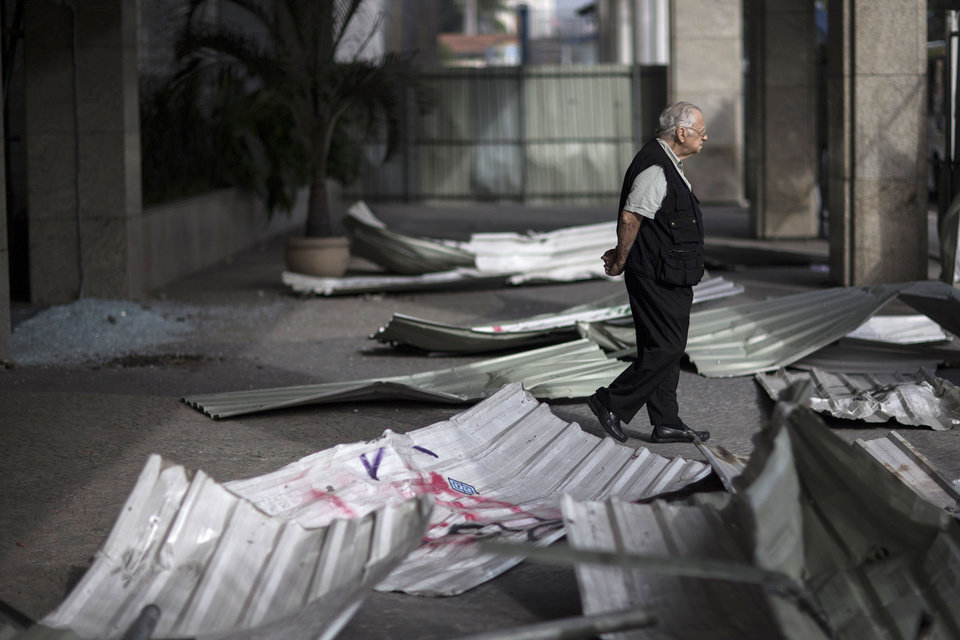 Photo - A man walks near the entrance of a commercial building that was damaged during protests in Rio de Janeiro, Brazil, Friday, June 21, 2013. Police and protesters fought in the streets into the early hours Friday as Brazilians swarmed through Brazilian cities in the biggest demonstrations yet against a government viewed as corrupt at all levels and unresponsive to its people. President Dilma Rousseff called an emergency meeting of her top Cabinet members for Friday morning, more than a week after the protests began. (AP Photo/Felipe Dana)
