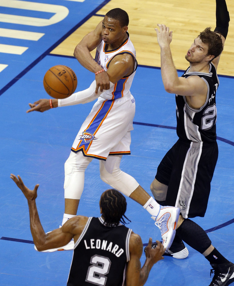 Photo - Oklahoma City's Russell Westbrook (0) passes the ball as San Antonio's Tiago Splitter (22) and Kawhi Leonard (2) defend during Game 2 of the Western Conference semifinals in the NBA playoffs between the Oklahoma City Thunder and the Los Angeles Clippers at Chesapeake Energy Arena in Oklahoma City, Monday, May 7, 2014. Photo by Bryan Terry, The Oklahoman