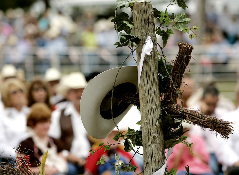 Photo - Jim Shoulders' hat rests on a memorial arrangement during his funeral services in Henryetta, Okla., on Sunday,  June 24, 2007. By John Clanton, The Oklahoman