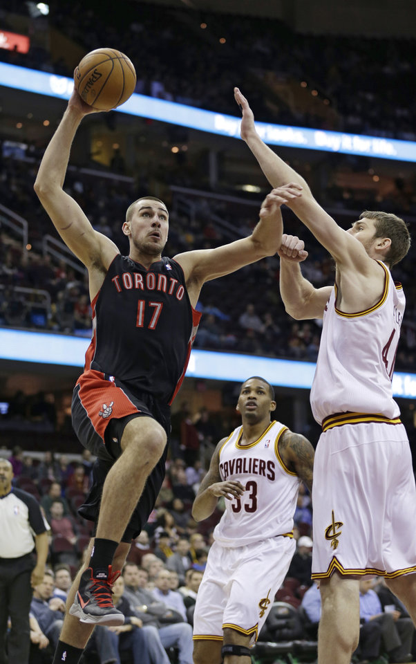 Toronto Raptors' Jonas Valanciunas (17) jumps to the basket against Cleveland Cavaliers' Tyler Zeller, right, during the first quarter of an NBA basketball game Wednesday, Feb. 27, 2013, in Cleveland. (AP Photo/Tony Dejak)