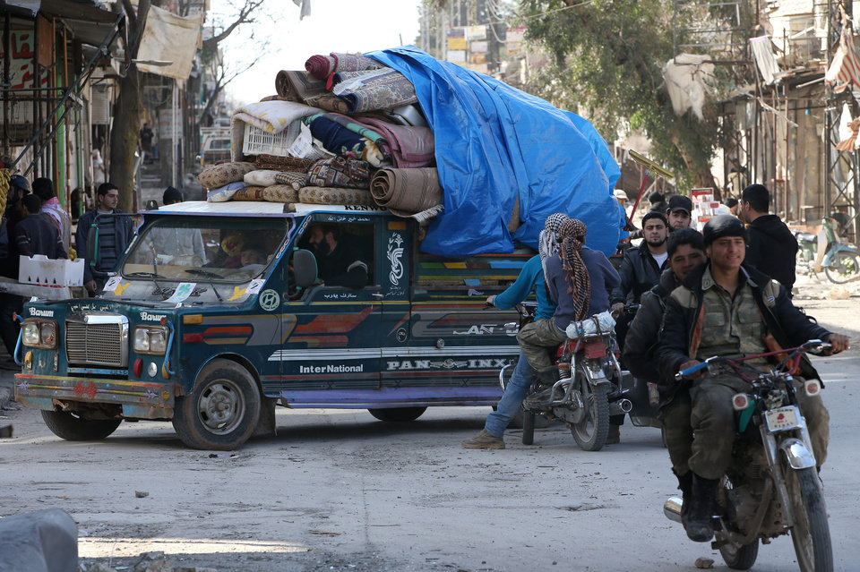 Photo - A Syrian family carry their house furniture on a pickup as they leave their home to a safer place, at Maarat al-Nuaman town, in Idlib province, Syria, Tuesday Feb. 26, 2013. Syrian rebels battled government troops near a landmark 12th century mosque in the northern city of Aleppo on Tuesday, while fierce clashes raged around a police academy west of the city, activists said. (AP Photo/Hussein Malla)