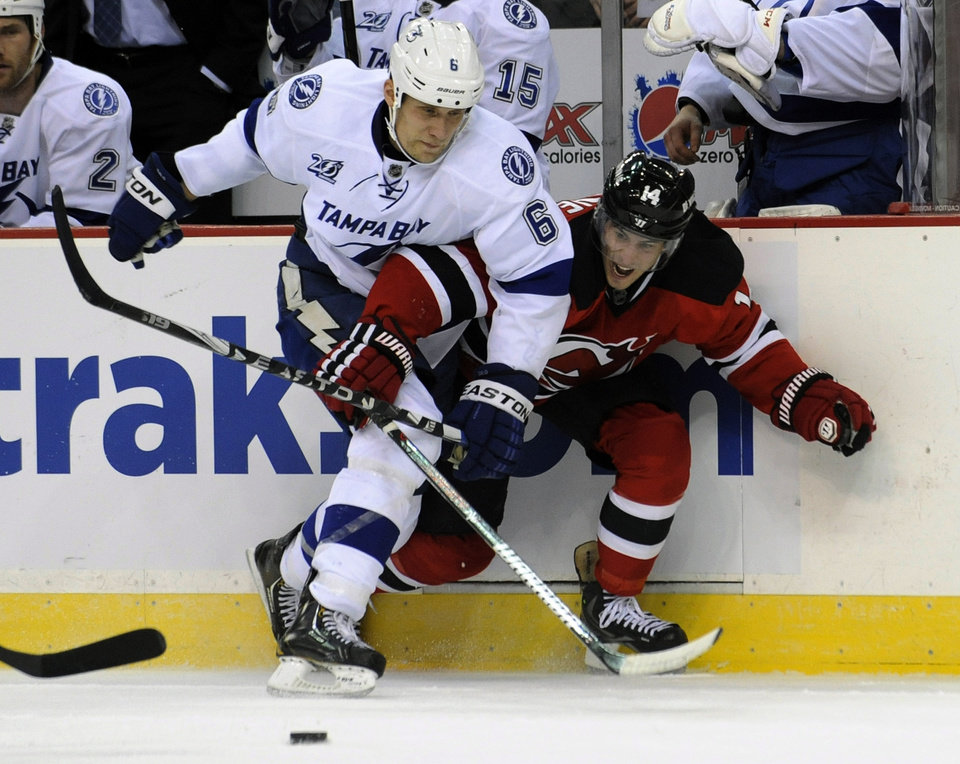 New Jersey Devils' Adam Henrique, right, battles along the boards with  Tampa Bay Lightning's Sami Salo, of Finland, during the first period of an NHL hockey game Tuesday, March 5, 2013, in Newark, N.J. (AP Photo/Bill Kostroun)