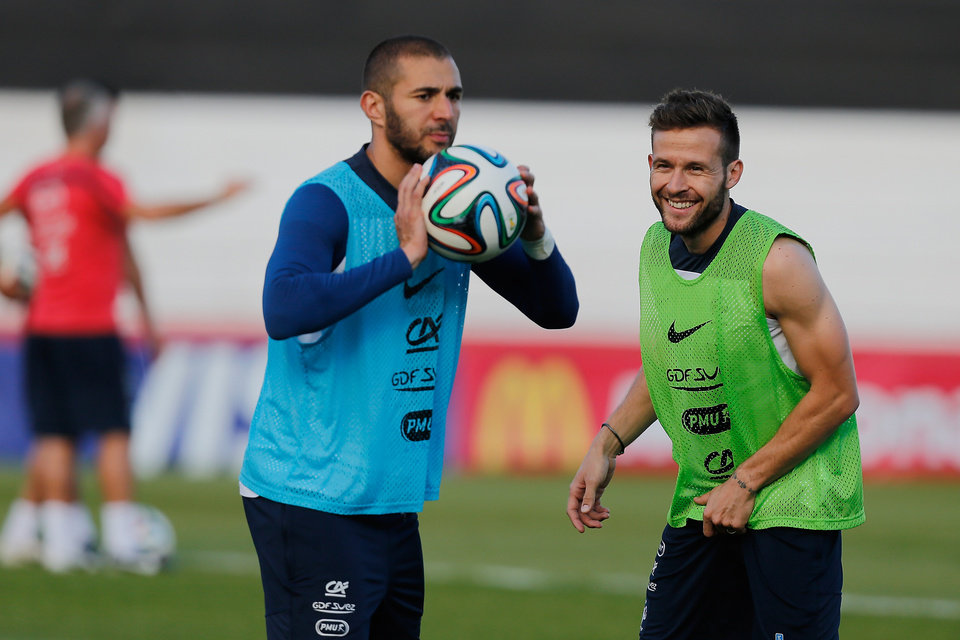 Photo - France's Yohan Cabaye, green shirt, smiles while Karim Benzema, in blue, holds a soccer ball, during a training session of the French national soccer team at the Santa Cruz Stadium in Ribeirao Preto, Brazil, Wednesday, June 11, 2014. France will face Ecuador, Switzerland and Honduras in group E of the 2014 Soccer World Cup. (AP Photo/David Vincent)