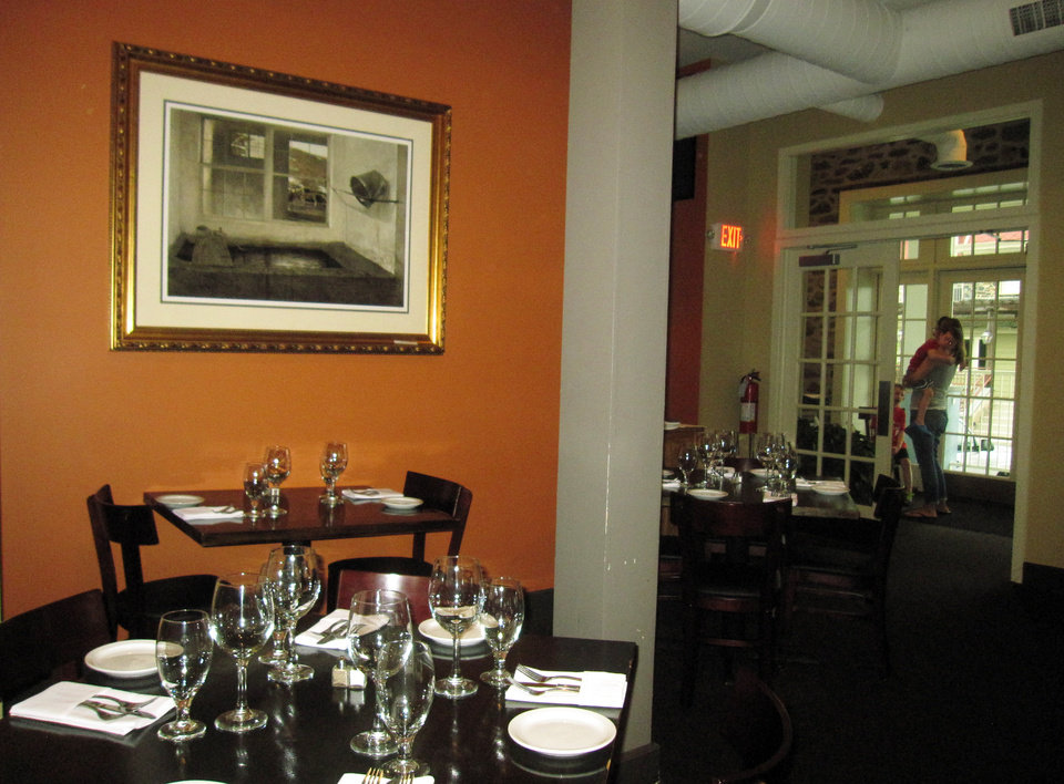 Photo - This May 28, 2014 photo shows the dining room at Antica, a restaurant in Chadds Ford, Pa. The restaurant is located near the Brandywine River Museum, which has an extensive collection of artwork by the Wyeth family and offers tours of nearby homes and studios where N.C. Wyeth, his son Andrew Wyeth and grandson Jamie Wyeth lived and worked. The restaurant is decorated with prints of Wyeth artwork. (AP Photo/Beth J. Harpaz)
