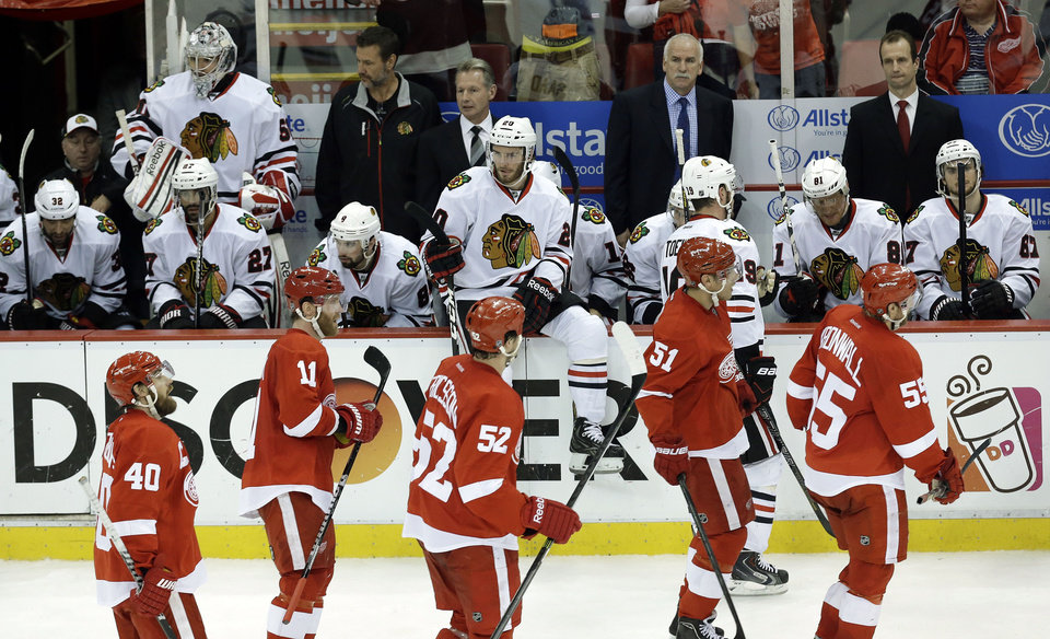 Photo - Detroit Red Wings, foreground, skate past the Chicago Blackhawks bench after Daniel Cleary's empty-net goal during the third period in Game 4 of the Western Conference semifinals in the NHL hockey Stanley Cup playoffs in Detroit, Thursday, May 23, 2013. Detroit won 2-0. (AP Photo/Paul Sancya)