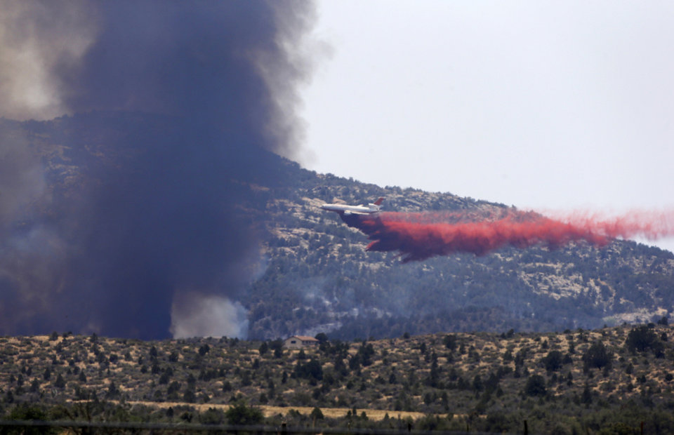 Photo - An aerial tanker drops fire retardant on a wildfires threatening homes near Yarnell, Ariz., Monday, July 1, 2013. An elite crew of firefighters was overtaken by the out-of-control blaze on Sunday, killing 19 members as they tried to protect themselves from the flames under fire-resistant shields. (AP Photo/Chris Carlson)