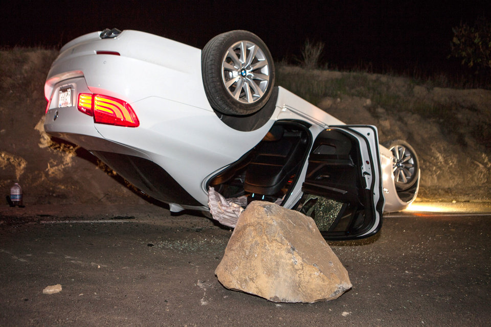 Photo - A car sits overturned on a highway in the Carbon Canyon area of Brea, Calif., Friday night, March 28, 2014, after hitting a rock slide caused by an earthquake. The people inside the car sustained minor injuries. A magnitude-5.1 earthquake centered in the area near Los Angeles caused no major damage but jittered nerves throughout the region as dozens of aftershocks struck into the night. (AP Photo/Kevin Warn)