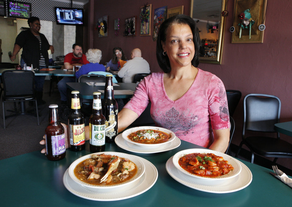 Thais Goodwin with bowls of seafood gumbo, crawfish etouffee, and shrimp creole prepared at the Bayou Grill and Bakery in Edmond. <strong>PAUL B. SOUTHERLAND - THE OKLAHOMAN</strong>