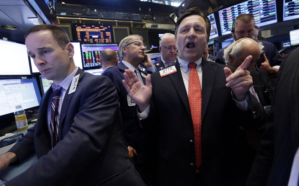 Photo - Specialist Thomas Facchine, right, calls out prices during the IPO of Eclipse Resources Corp. on the floor of the New York Stock Exchange, Friday, June 20, 2014. Stocks are slightly higher in early trading as the market heads for a week of solid gains. (AP Photo/Richard Drew)