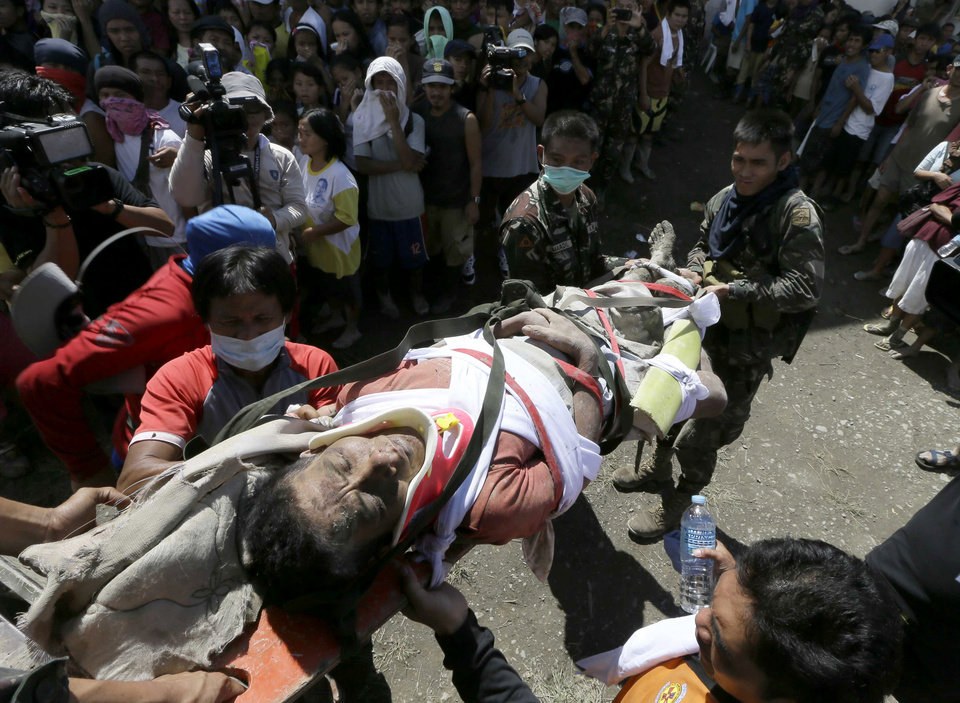 A survivor of Tuesday's devastating typhoon is carried into a makeshift clinic after being rescued Thursday, Dec. 6, 2012, in New Bataan township, Compostela Valley in the southern Philippines.  The powerful typhoon that washed away emergency shelters, a military camp and possibly entire families in the southern Philippines has killed hundreds of people with nearly 400 missing, authorities said Thursday. (AP Photo/Bullit Marquez)