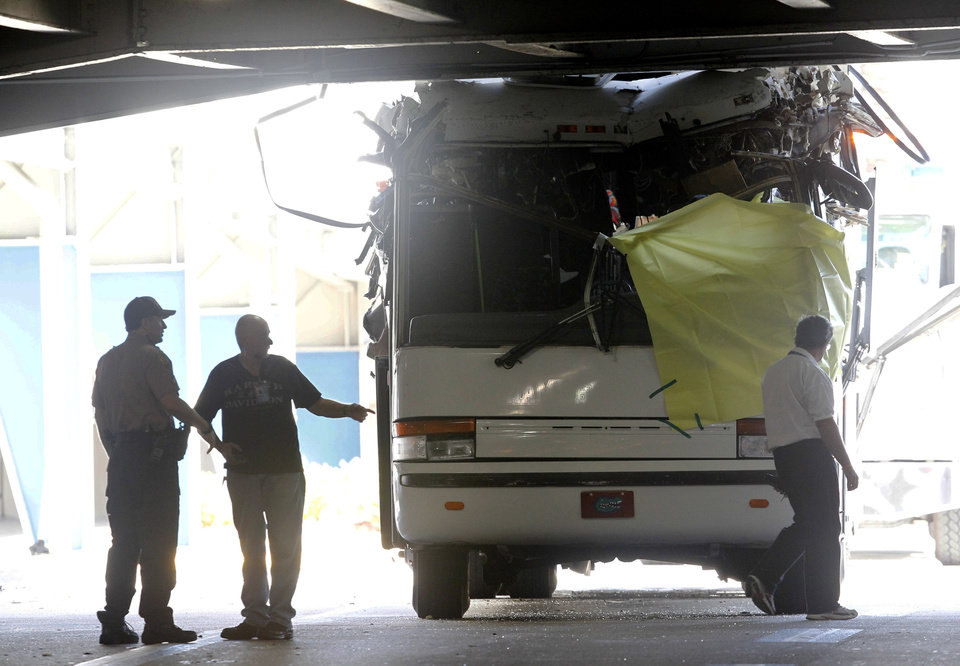 Photo - Law enforcement officers stand next to a bus after it hit a concrete overpass at Miami International Airport in Miami on Saturday, Dec. 1, 2012. The vehicle was too tall for the 8-foot-6-inch entrance to the arrivals area, and buses are supposed to go through the departures area which has a higher ceiling, according to an airport spokesperson. (AP Photo/Wilfredo Lee)