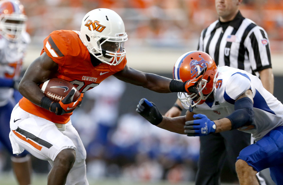 Photo - Oklahoma State's Desmond Roland (26) gets by Vaughn Cornelia (9) during a college football game between Oklahoma State University (OSU) and Savannah State University at Boone Pickens Stadium in Stillwater, Okla., Saturday, Sept. 1, 2012. Photo by Sarah Phipps, The Oklahoman