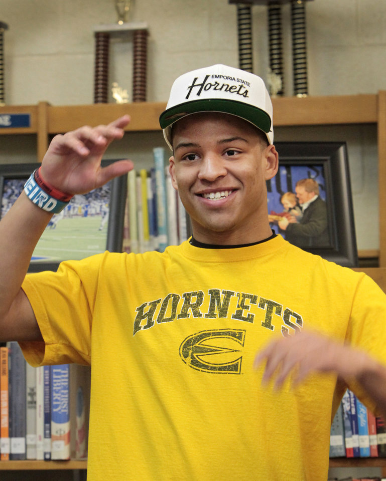 Football player Kai Callins, puts on his Hornets cap during signing of his letter of intent to play for Emporia State at Guthrie High School, Wednesday, February 4, 2014. Photo by David McDaniel, The Oklahoman