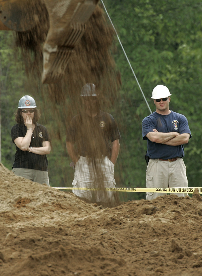 Photo -   FILE - In this May 26, 2006, file photo Federal Bureau of Investigation agents investigating Jimmy Hoffa's 1975 disappearance examine a dig site where a barn once stood at a horse farm in Milford Township, Mich. (AP Photo/Paul Sancya, File)