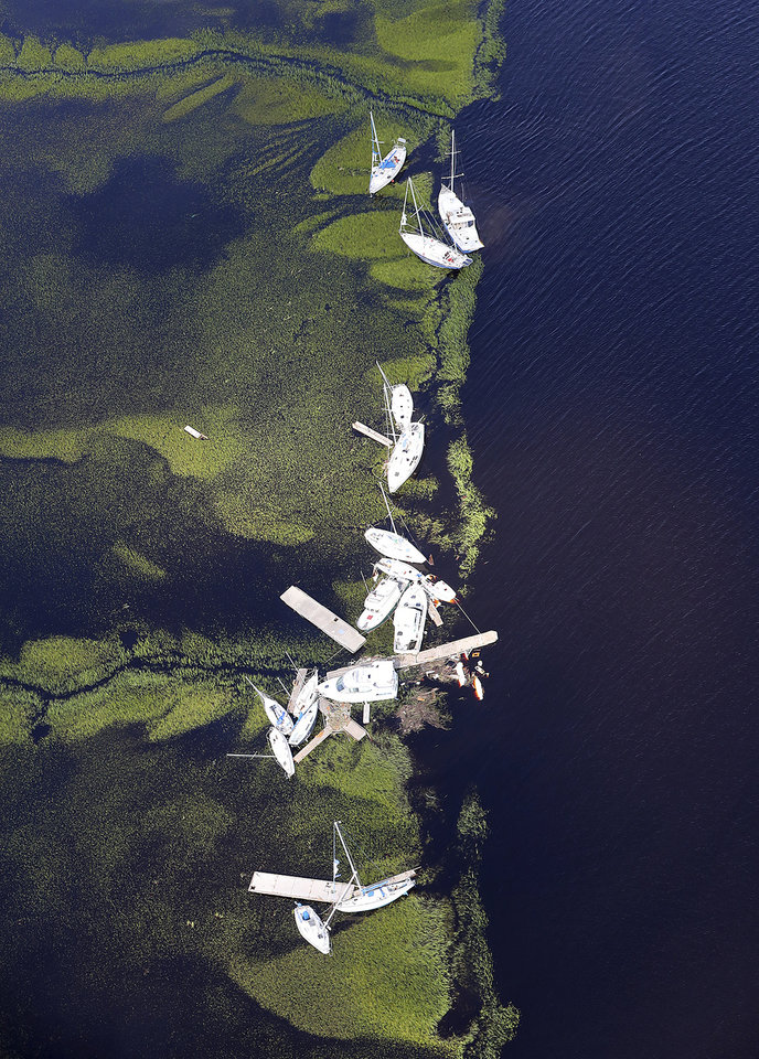 Photo - Boats blown away from their docks sit in the marsh after Hurricane Irma on Tuesday, Sept. 12, 2017, at St. Marys on the Georgia coast. (Curtis Compton/Atlanta Journal-Constitution via AP)